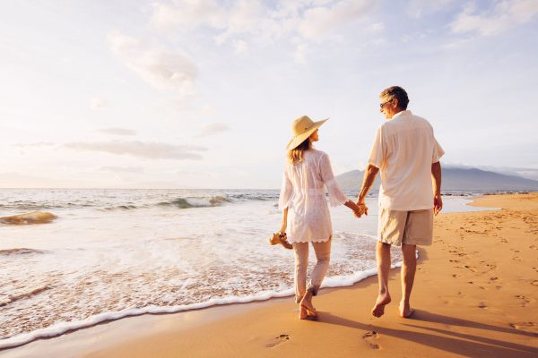 49643698 - happy romantic middle aged couple enjoying beautiful sunset walk on the beach. travel vacation retirement lifestyle concept